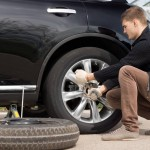 un homme accroupi change une roue