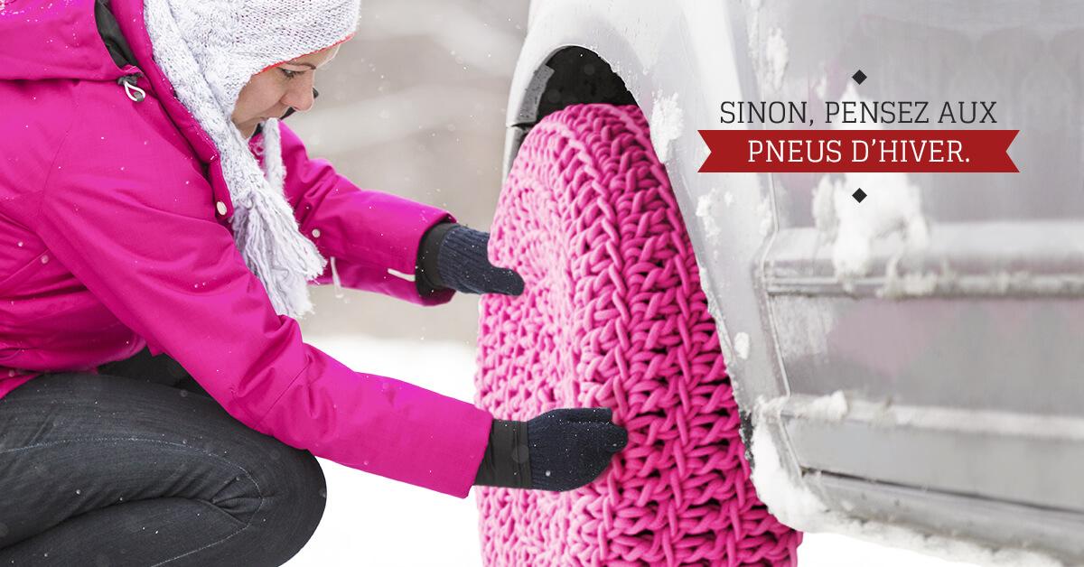 femme accroupie dans la neige installe une protection en laine rose sur une roue de voiture