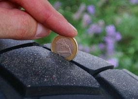 une pièce de 1 euro placée dans la rainure d'un pneu